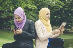 Stile di vita di tecnologia e di urbano, giovane muslimah che si siede su un'erba verde al parco Fotografia Stock Libera da Diritti