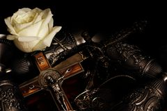 Stiletto, crucifix with inlaid metal chain, metal goblets for wine and white rose on black background. Souvenirs from Germany. stock photography