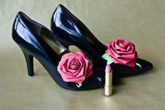 Stiletto heels. Black high heel shoes & paper flowers & lipstick Stock Photos