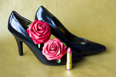 Stiletto heeled shoes. Black high heel shoes, paper roses and a lipstick Stock Photos