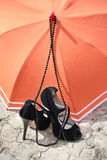 Stiletto heels, necklace and umbrella on a cracked earth. Black stiletto heels and necklace with orange umbrella on a cracked earth Royalty Free Stock Images