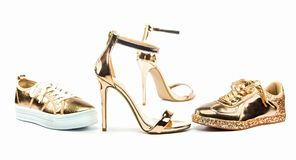 Stiletto high heels and sneakers in metallic colors. Sexy stiletto high heels with ankle strap and fashionable sneakers in shiny metallic color,  on white Royalty Free Stock Photos