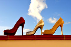 Stiletto shoe against sky in sunshine. Three high heels shoes against summer sky stock photography