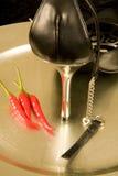 Stiletto sul cassetto d'argento con i peperoncini rossi Fotografia Stock