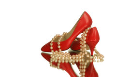 Stilettos with pearls. Pair of red stilettos shoes with pink pearls isolated and reflected on white Stock Image