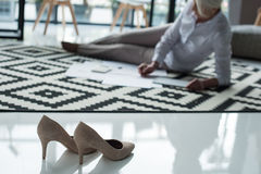 Stilettos and senior businesswoman working with documents on floor Royalty Free Stock Image