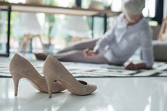 Stilettos and senior businesswoman working with documents on floor Stock Photo