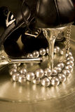 Stilettos and a string of pearls on a tray. Closeup of black stilettos with silver heels and a string of pearls on a silver tray Royalty Free Stock Photography