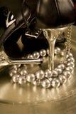 Stiletts und eine Zeichenkette der Perlen auf einem Tellersegment Lizenzfreie Stockfotografie