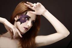 Stilflicka med makeup- och violetblomman. Royaltyfria Foton