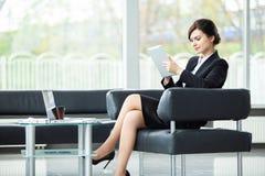 Stilfull affärskvinna som sitter på soffan genom att använda minnestavlaPC i kontoret arkivfoto