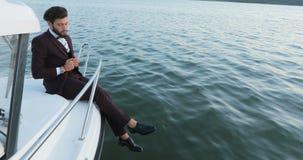 Stilfull affärsman på en yacht eller ett fartyg mot ett hav Han behas med framgången i hans affär och hans lag lager videofilmer