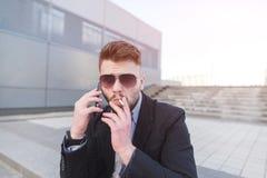 Stilfull affärsman som talar på telefonen och röker en cigarett arkivfoto