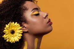 Stilfull afrikansk amerikankvinna med konstnärligt smink och gerbera, i att drömma för hår fotografering för bildbyråer