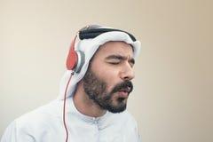 Stilfull arabisk man i hörlurar, arabisk grabb som lyssnar till musik Fotografering för Bildbyråer