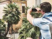 Stilfull attraktiv handelsresande med smartphonen som fotograferar gammal byggnad arkivbild