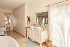 Stilfull badrum- och sovruminre i ett modernt förorts- hem royaltyfri fotografi