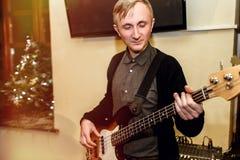 Stilfull bas- gitarrist som spelar på en konsert på en bakgrund av H arkivbilder