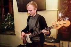 Stilfull bas- gitarrist som spelar på en konsert på en bakgrund av H arkivfoto