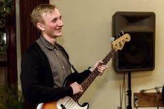 Stilfull bas- gitarrist som spelar på en konsert på en bakgrund av H fotografering för bildbyråer