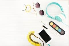 Stilfull bild av tillbehör för kvinna s över på ljus träbakgrund Gul dekorering, halsband, telefon arkivfoton