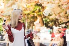 stilfull blond flicka som rymmer pappers- påsar och ser attrapper arkivfoto