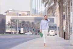 Stilfull blond kvinna i smart tillfällig blus och vita trouses Fotografering för Bildbyråer