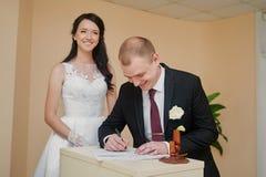Stilfull brudgum som ser hans undertecknande bröllopregister för härlig brud Royaltyfri Fotografi