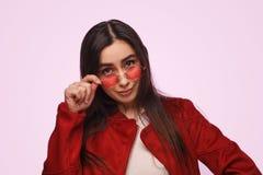 Stilfull brunett i den röda dräkten som ser säker fotografering för bildbyråer