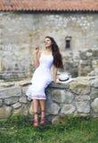 Stilfull brunettkvinna i den vita klänningen på wal bakgrund av tegelsten Arkivbilder