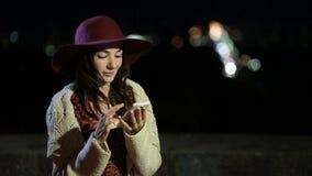 Stilfull brunettkvinna som använder smartphonen på natten lager videofilmer