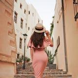 Stilfull brunettkvinna som går i gammal stad royaltyfri foto