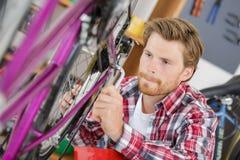Stilfull cykelmekaniker som gör yrkesmässigt arbete i seminarium royaltyfria foton