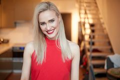 Stilfull elegant blond kvinna i hem- vardagsrum, bärande röd sexig klänning royaltyfri bild