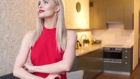 Stilfull elegant blond kvinna i hem- vardagsrum, bärande röd sexig klänning lager videofilmer