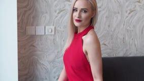 Stilfull elegant blond kvinna i hem- vardagsrum, bärande röd sexig klänning arkivfilmer