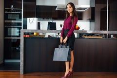Stilfull elegant dam hemma, når att ha shoppat att kika in i påsarna som granskar henne köp royaltyfria bilder