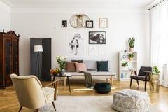 Stilfull fåtölj och puff på den hemtrevliga mattan i flott vardagsrum som är inre med grått soffa- och tappningmöblemang royaltyfri foto
