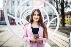 Stilfull flicka för stadslivsstil som använder en telefon som smsar på smartphonen app i en gata nära den moderna bänken Royaltyfri Foto