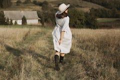 Stilfull flicka i den linneklänningen och hatten som kör och ler i soligt fältgräs på byn i berg Boho kvinna som in kopplar av royaltyfria bilder
