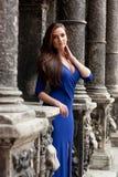 Stilfull flicka i ett blått klänninganseende bredvid den bra gamla väggen Fotografering för Bildbyråer