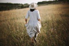 Stilfull flicka i linneklänningen som kör bland örter och vildblommor i solig äng i berg Boho kvinna som kopplar av i bygd, arkivfoto