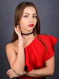 Stilfull flicka i röd klänninghals med den svarta tättsittande halsband arkivfoton