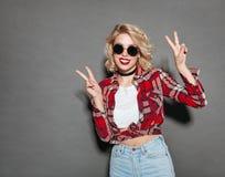 Stilfull flicka som gör en gest och ler royaltyfri fotografi