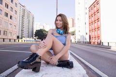 Stilfull flicka som sitter i gatan utan trafik, inga bilar Full längd av kvinnan med ben som korsas med byggnader i baksidan royaltyfri fotografi