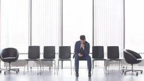 Stilfull grabb för ensamt mode som sitter på stol och använder telefonen lager videofilmer