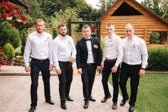 Stilfull groomsman med brudgummen som står på trädgården och att förbereda sig för den gifta sig ceremonin Vännen spenderar tid t arkivbilder
