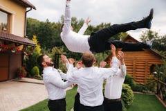 Stilfull groomsman med brudgummen som står på trädgården och att förbereda sig för den gifta sig ceremonin Vännen spenderar tid t arkivfoto