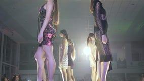 Stilfull händelse, grupp av modeller in i modeklänningen och hög-heeled skodonställning på podiet i belysning framme av lager videofilmer