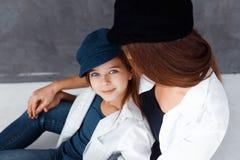 Stilfull härlig moder och en gullig dotter med blåa ögon, i att krama för studio bärande hattar för mamma och för dotter royaltyfria foton